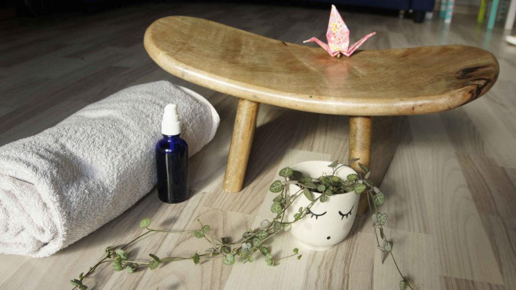 Huile de massage, linge blanc, plante verte dans un pot avec un visage apaisant et un petit banc où se trouve une cocotte en papier